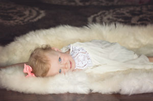 Photo of a small toddler laying on a fur blanket for Toddler Sleep Training Services | The Peaceful Sleeper
