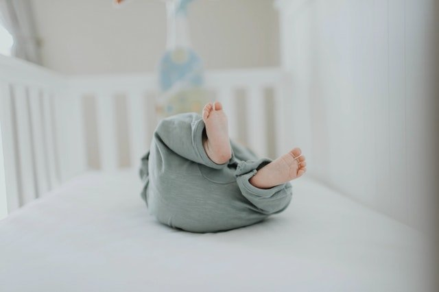 A 1 week old baby in a crib while parents are learning how to get a newborn to sleep from an infant sleep consultant