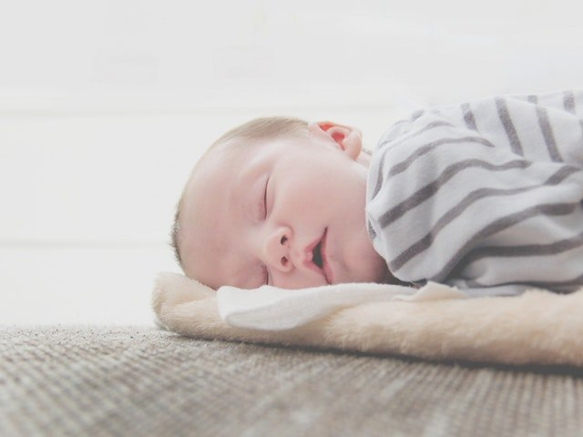 Photo of a baby sleeping after the parents used an infant sleep consultant to sleep train their baby.