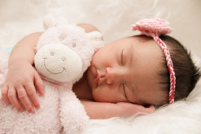 2 week old baby girl sleeping on a white rug with a stuffed animal - newborn sleep training course available from an infant sleep consultant