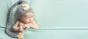 Newborn baby in fuzzy hat with long tassel sleeping soundly between blue sheets after taking The Peaceful Sleeper's online Newborn Essentials Sleep Course | How to make newborn sleep through the night
