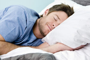 Man comfortably sleeping in his bed with eyes closed and smile on his face after taking The Peaceful Sleeper's Online Adult Insomnia Course